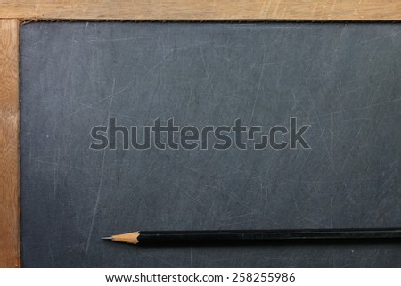 Vintage and old slate blackboard and wooden pencil put on the black color leather background represent the teaching equipment related.