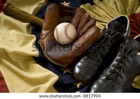 Vintage, antique baseball gear on vintage American flag bunting, inlcuding a baseball mitt or glove, baseball shoes or cleats, a baseball bat and a baseball. sports background