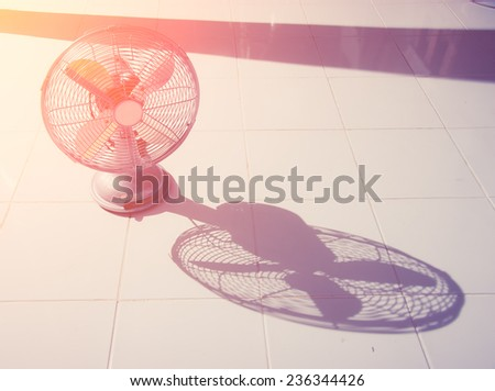 vintage Antique fan and shadow on tiled floor - stock photo