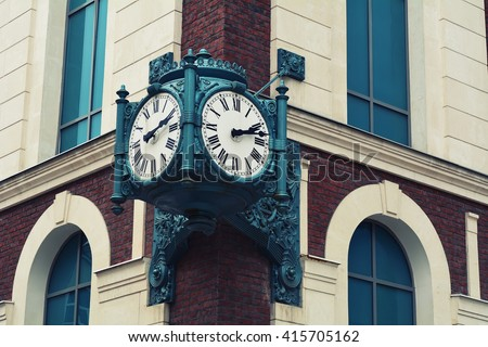 Vintage antique old clock hanging on a brick building - stock photo
