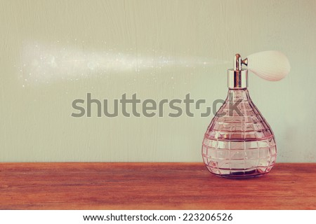 vintage antique perfume bottle with effect of perfume spray, on wooden table. retro filtered image - stock photo