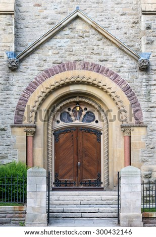 Vintage architecture doors at the University of Toronto. The brown wooden doors are set in an archway in a white stone wall, with white stone steps leading up to them. - stock photo