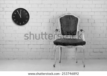 Vintage armchair against brick wall with clock. Converted in B&W - stock photo