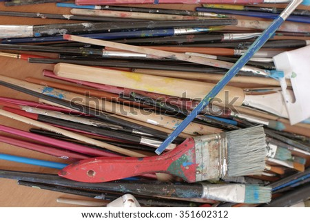 Vintage artists brushes and paint tubes on an abstract artistic background - stock photo