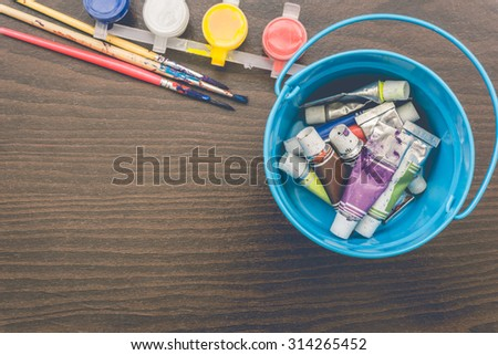 Vintage artists brushes and paint tubes on wooden table. - stock photo