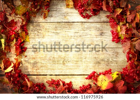 Vintage Autumn border from ashberry and and fallen leaves on old wooden table/Thanksgiving day concept/ - stock photo