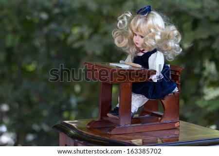 Vintage baby doll in school uniform seated at desk, sold on flea market in Slovenia - stock photo