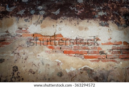 Vintage background of old brick wall with cracked concrete area.