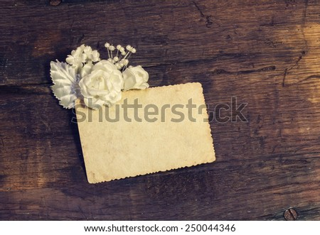 Vintage background with artificial flowers and a note - stock photo