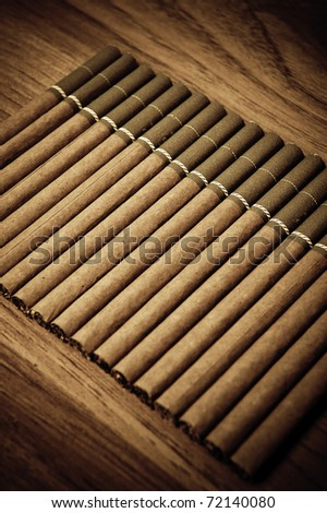 Vintage background with cigarettes on brown wooden background - stock photo