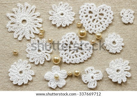 Vintage background with cotton lace crochet elements: hearts, pearls and flowers. Knitted background on linen cloth.  Knitted frame with handmade lace. Christmas and Valentine's day background - stock photo