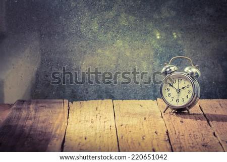 Vintage background with retro alarm clock on table. - stock photo