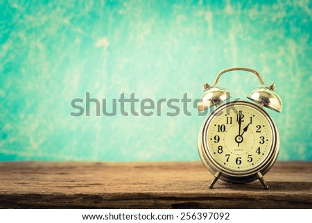 Vintage background with retro alarm clock on table - stock photo