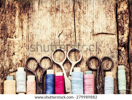 Vintage Background with sewing tools and colored tape/Sewing kit. Scissors, bobbins with thread and needles on the old wooden background - stock photo