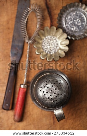 Vintage  Baking utensils - sifter, whisk, spatula, tins and moulds on wooden board - stock photo