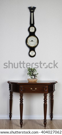 Vintage barometer, clock, thermometer under the wooden table - stock photo
