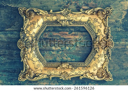 Vintage baroque golden frame on wooden background. Grunge wood texture. Retro style toned picture - stock photo