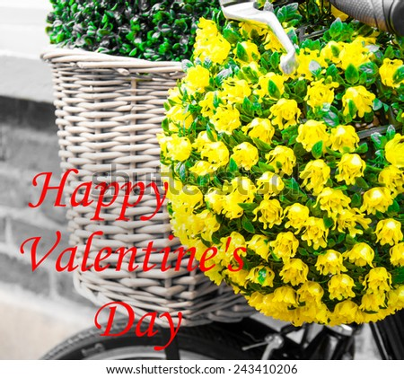 Vintage basket and flowers on bicycle with Happy Valentines Day greeting written with red letters in lower left hand side corner, love concept - stock photo