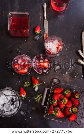 Vintage basket with strawberry, cups of homemade strawberry lemonade and ice cubes, strawberry jam over a dark background. See series. - stock photo