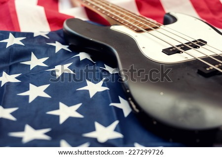 Vintage bass guitar on an american flag background. selective focus - stock photo