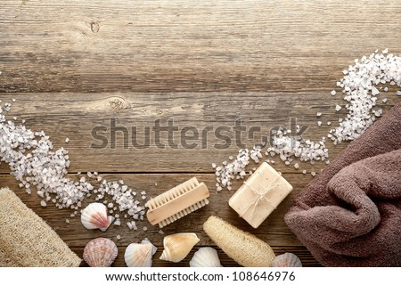 Vintage bath and retro body hygiene accessories with cleansing aromatherapy soap and brown towel decorated with seas shells and scattered bath salts over old worn wood planks spa background - stock photo