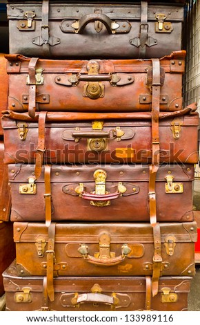 Vintage battered leather suitcases stacked vertically - stock photo