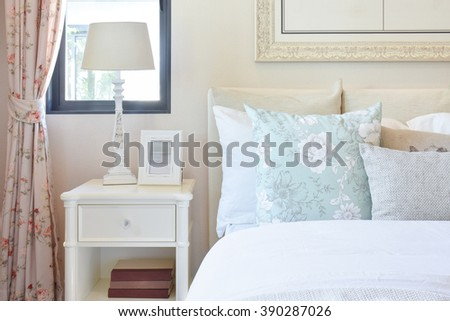 vintage bedroom interior with reading lamp and picture frame on white bedside table - stock photo