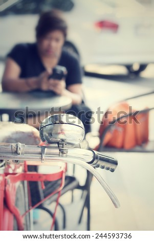 Vintage bicycle handlebar with woman using smart phone