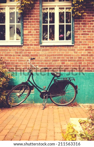 Vintage bicycle in Europe city near the wall - stock photo
