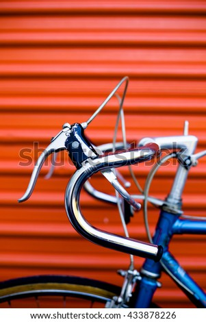Vintage bicycle in front of an orange garage door. Urban, city living, self storage, transportation and lifestyle concept - stock photo