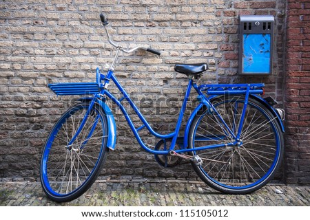 Vintage bicycle leaning against an old brick wall - stock photo