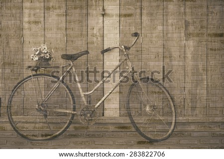 vintage bicycle on wooden house wall with a brick wall backdrop. - stock photo