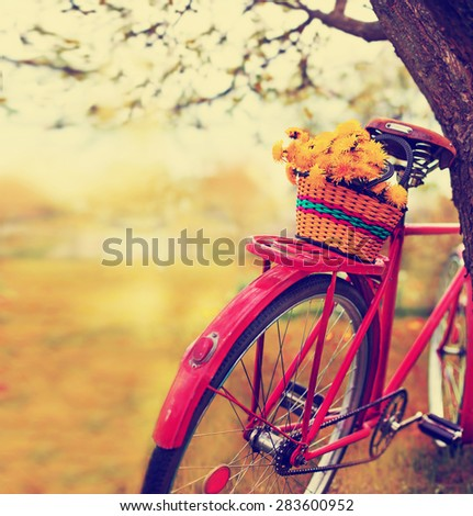 Vintage Bicycle with flowers on  landscape background (toned picture) - stock photo