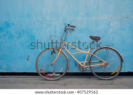 Vintage bicycle with old blue background - stock photo