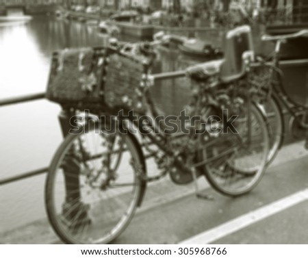 Vintage bike decorated with hearts and flowers on the bridge in Amsterdam (Netherlands). Blurred toned photo. Black and white. - stock photo