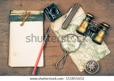 Vintage binoculars, notepad, compass, old map, ink pen, inkwell, pocket knife, magnifying glass on wooden background - stock photo
