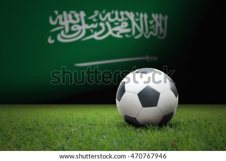 vintage black and white football ball on green grass has the national flag of Saudi Arabia background