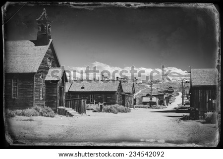 Vintage black and white old looking photo of empty streets of abandoned ghost town Bodie in California, USA in the middle of a day. - stock photo