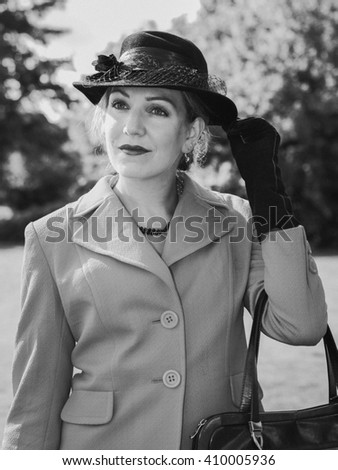 Vintage black and white portrait of a woman with a suit and a black hat looking dreamily