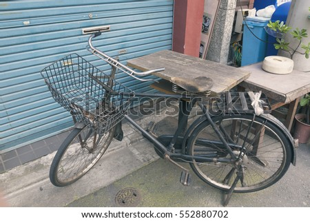 vintage black bicycle near wooden table in Tokyo