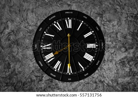 vintage black clock with a dark cement texture. grunge style of wallpaper/background