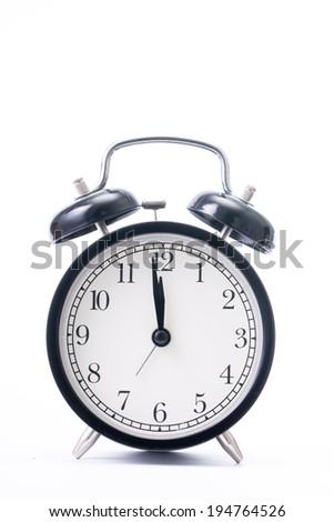 Vintage black color alarm clock on the write background - stock photo