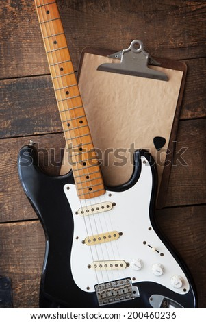 Vintage black double cutaway guitar on old wood surface and old clipboard, good for play lists, and production notes. one piece maple neck.  - stock photo