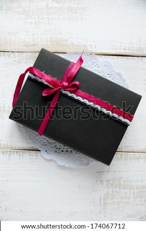 Vintage black gift box with red ribbon on a wooden background - stock photo