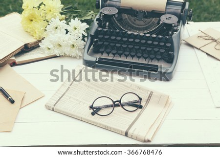 Vintage black typewriter with  old books and flowers on wooden table, outdoors - stock photo