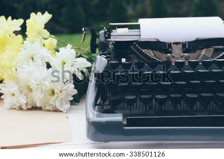 Vintage black typewriter with papers and flowers on wooden table, outdoors