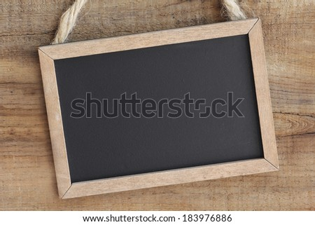 Vintage blackboard hanging on a wooden background with copy space - stock photo