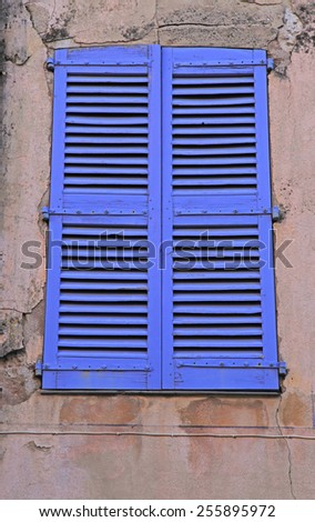 Vintage blue close window with shutters in old stone house, Provence, France. - stock photo