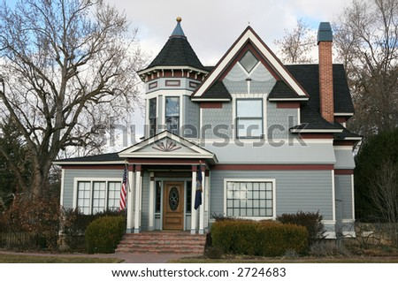 Vintage blue Victorian house with red and white trim and bare trees - stock photo