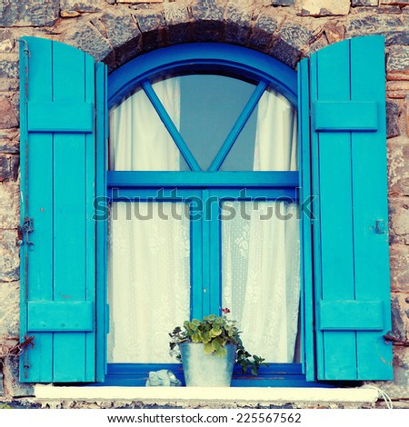 Vintage blue window and shutter with flower pot set in old stone wall, Crete, Greece. square toned image, instagram effect  - stock photo
